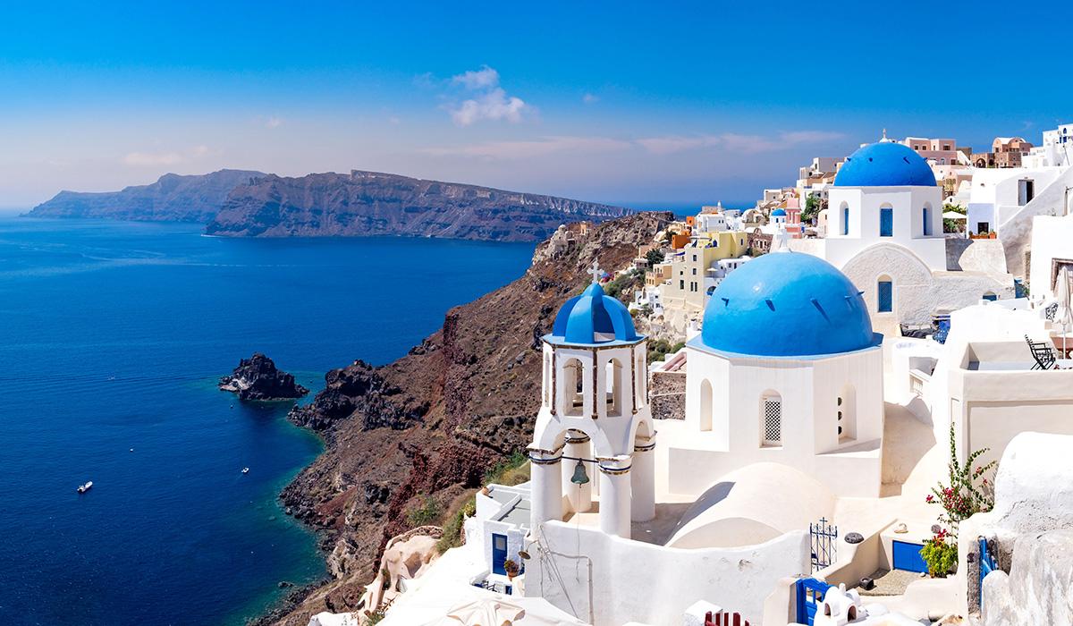 Typické bílé domy a jejich modré kupole ve městě Oia na Santorini.